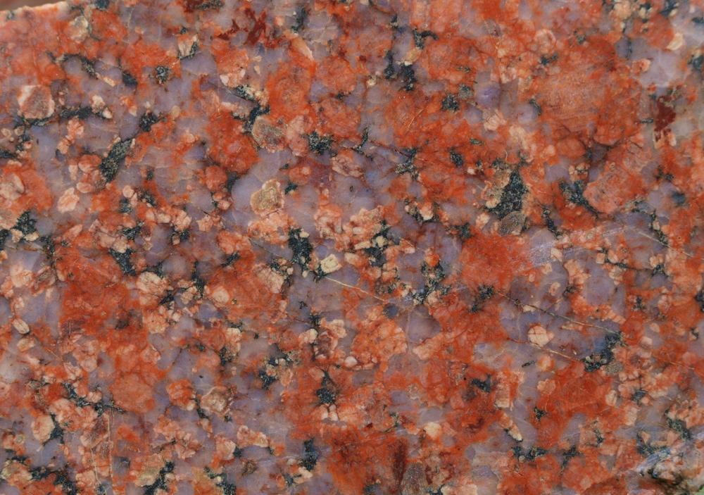 Der ausgestellte Vänge-Granit ermöglicht sehr gut das Studium der einzelnen Hauptminerale: der milchig-trübe Quarz besagt, dass der Granit nach seiner primären Erstarrung noch leicht metamorph überprägt wurde. In anderen Magmatiten kann der Quarz glasklar, transparent oder auch rauchgrau, gelblich oder bläulich sein. Der Kalifeldspat ist rot und die Plagioklase gelblich-weiß, teilweise grünlich und häufig zoniert, wie in obigem Foto links-mittig und darunter. Der Biotit ist Bestandteil der dunklen, teilweise vergrünten Aggregate.
